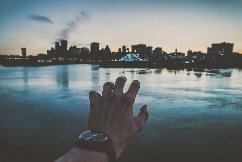 person's left hand reaching city scapes photography