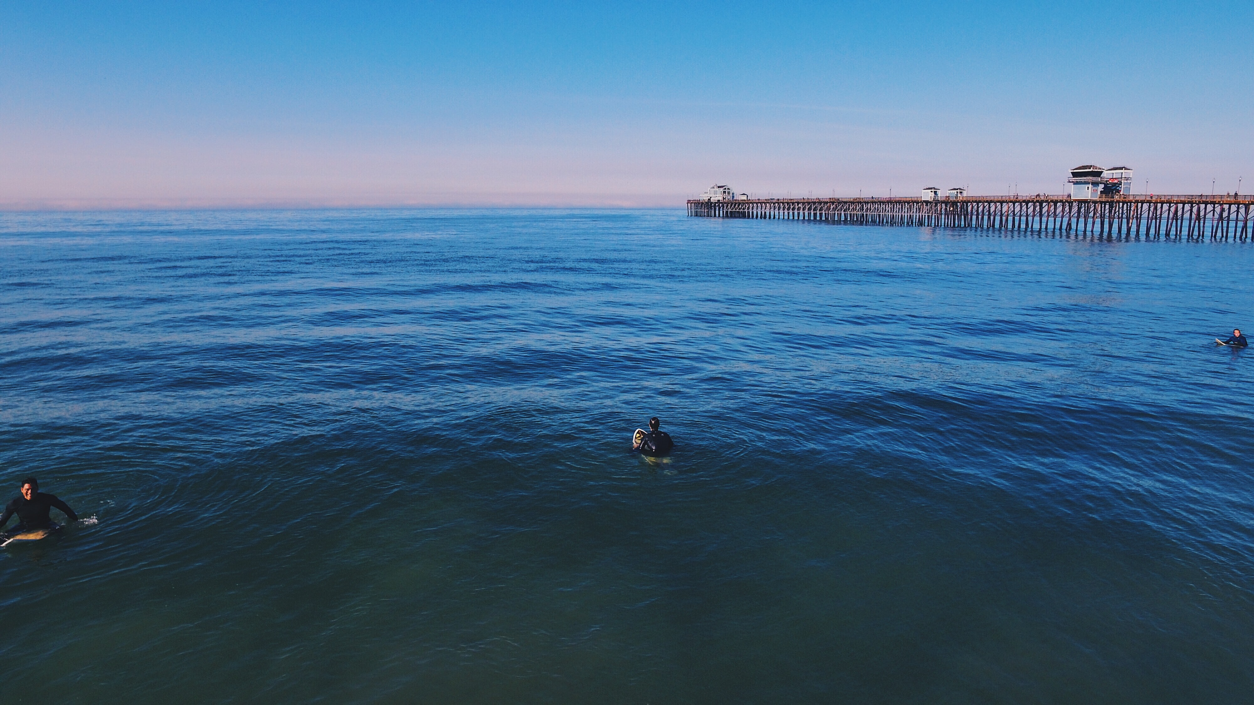 three people swimming on ocean under blue sky