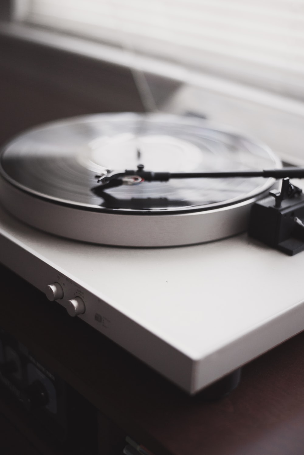 A blurry shot of a white record player playing a vinyl