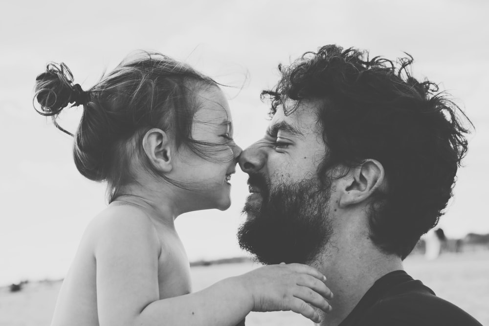 Father and daughter touch noses, smiling in black and white photo