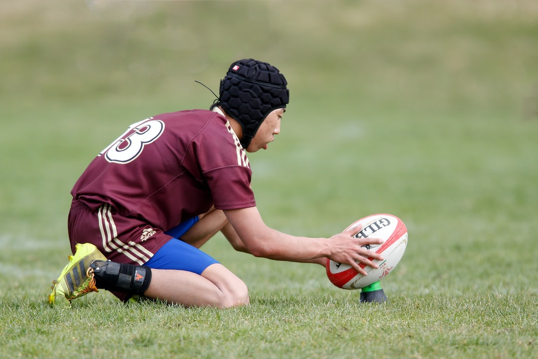 High school rugby player prepares to kick a conversion.