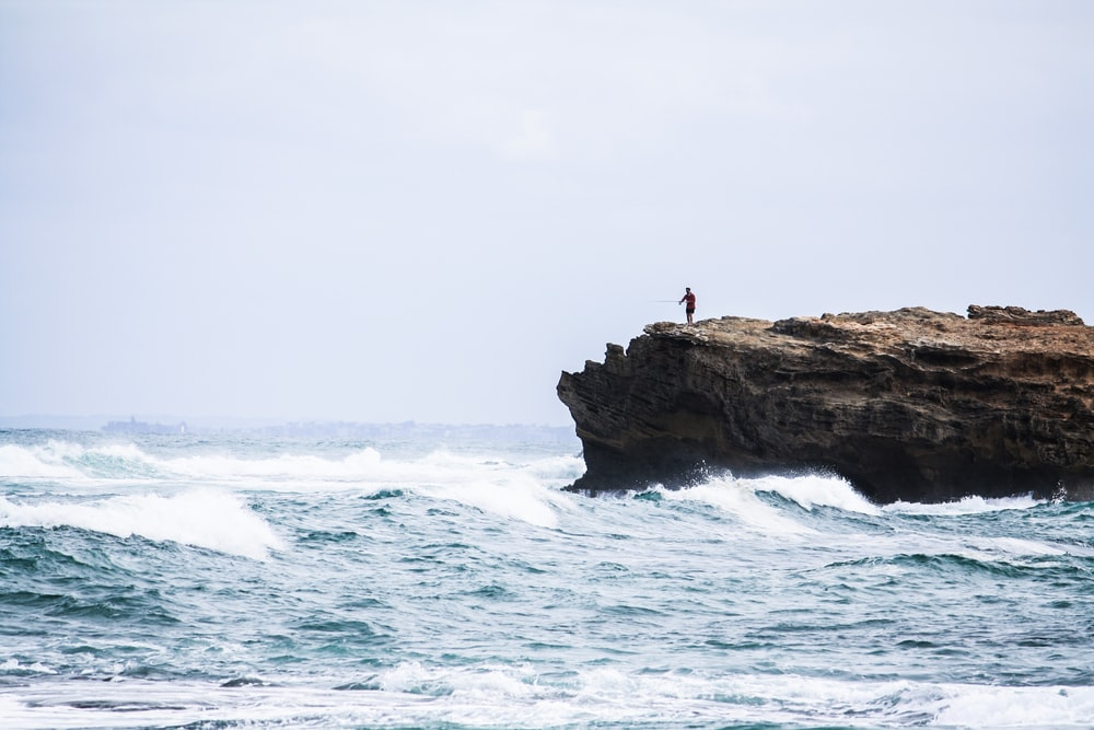 man standing on rock looking at the sea