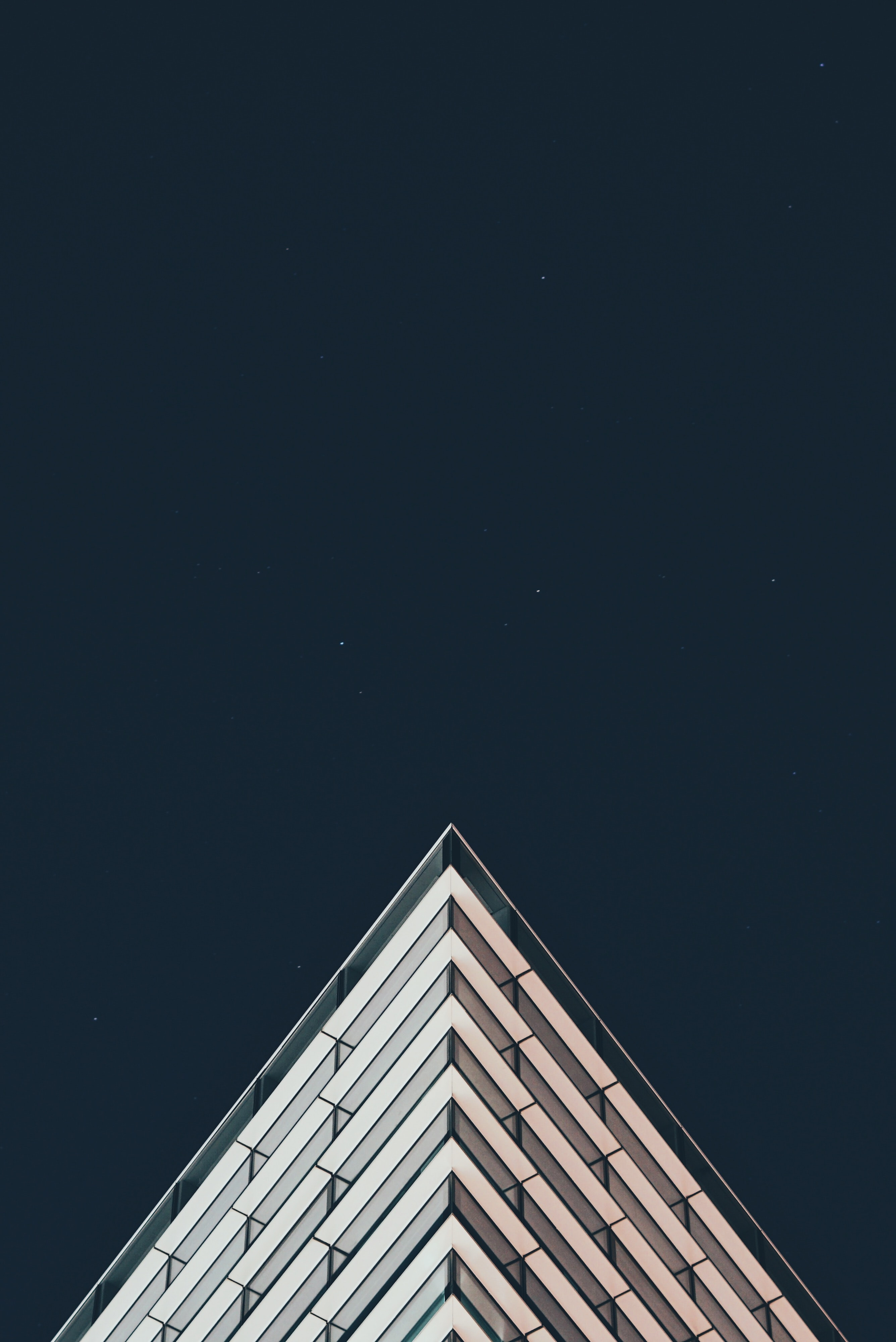 The sharp top corner of a modern building seen against the night sky