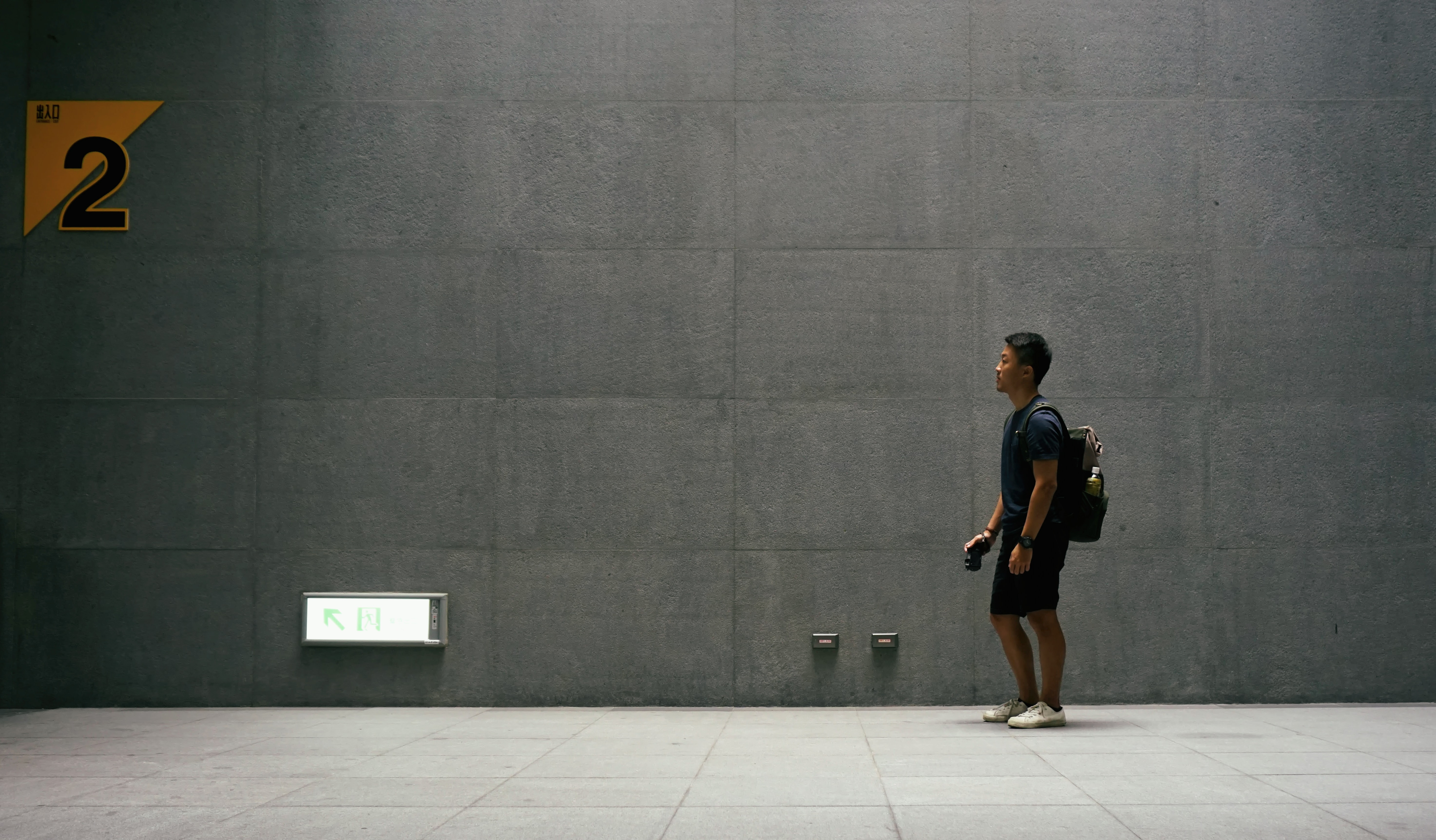 man in black top carrying backpack standing near wall