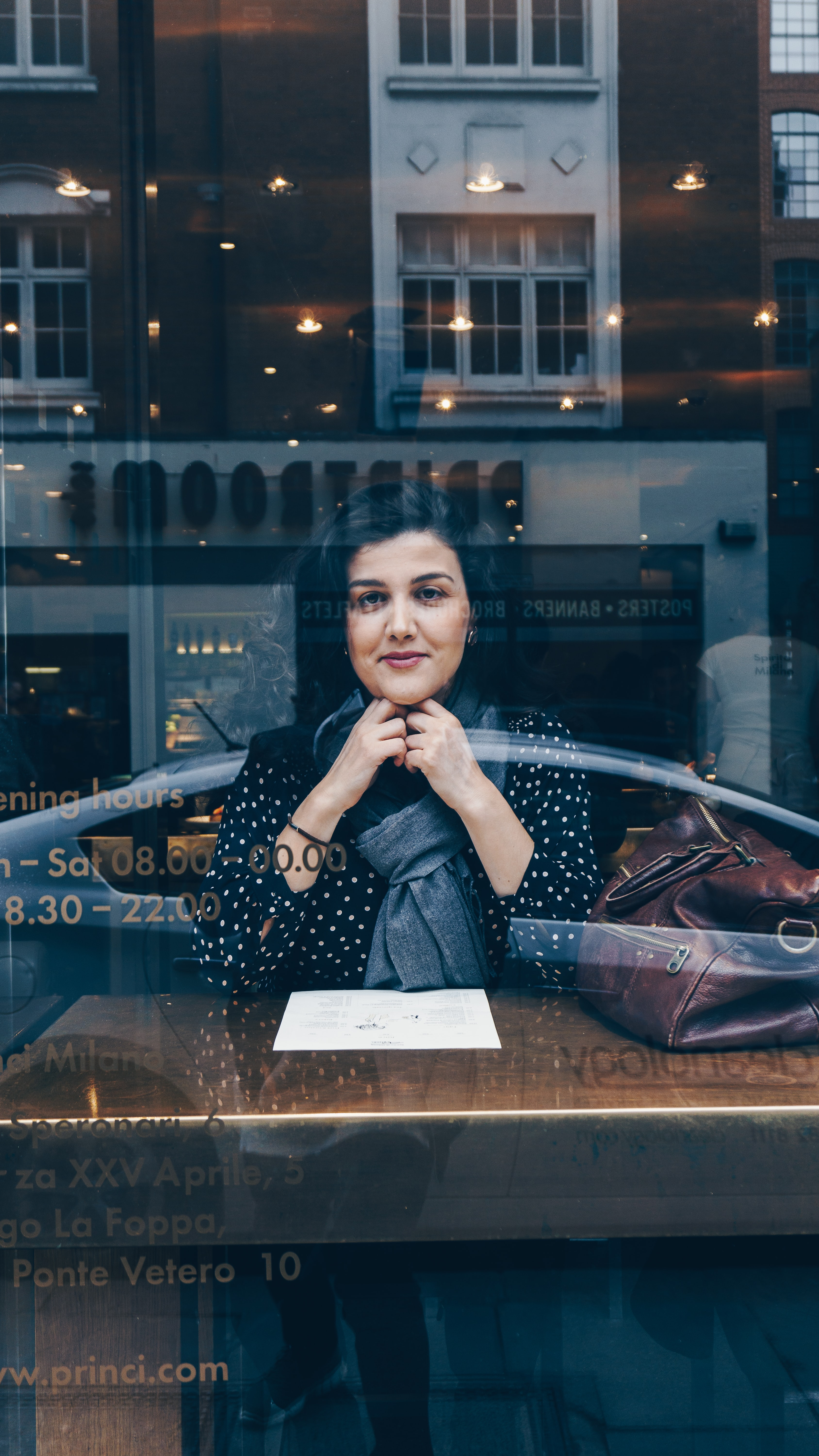 A woman leaning on her arms looks through a cafe window that reflects a city scene