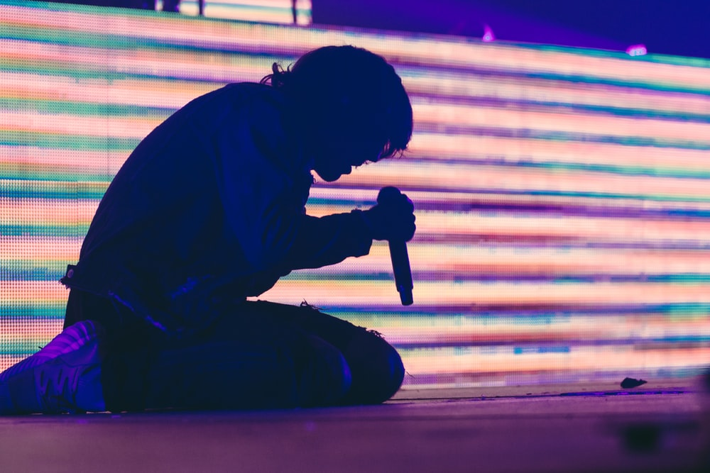 silhouette photo of man sitting on stage while holding dynamic wireless microphone