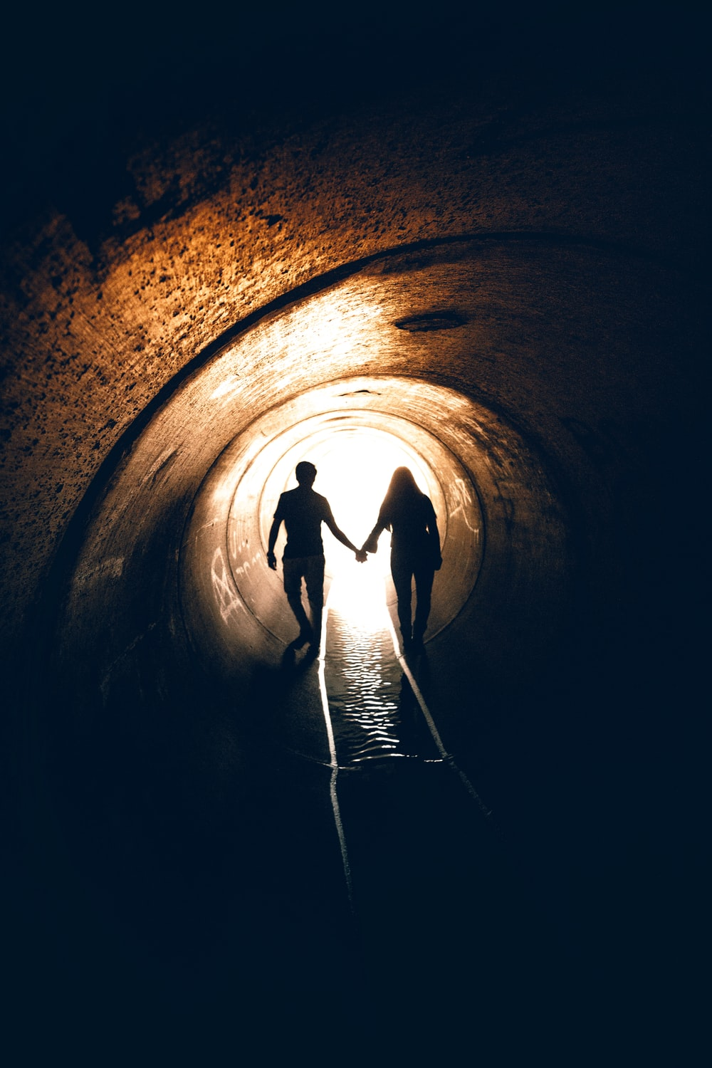 silhouette of man and woman inside tunnel