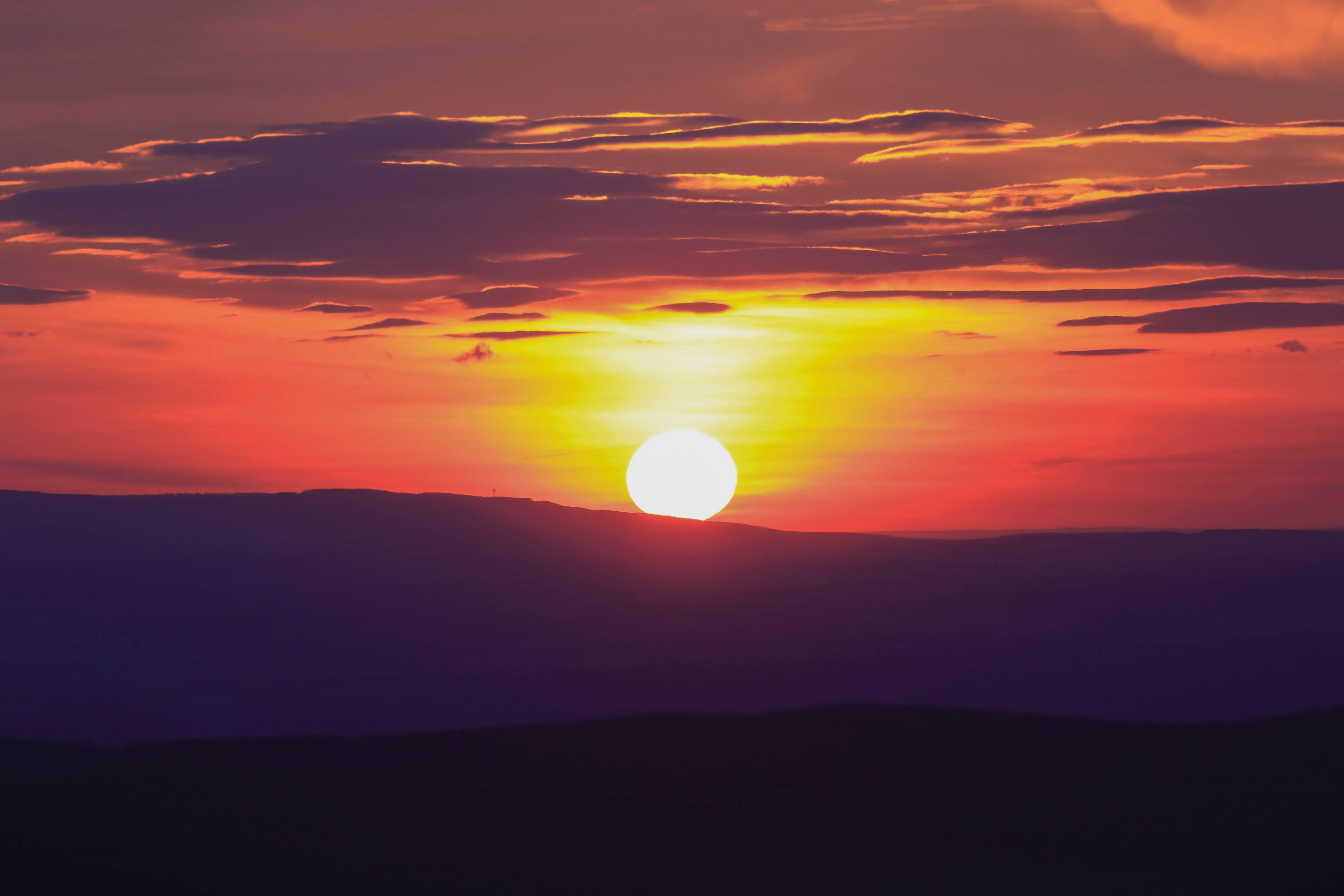 A red and orange sunset with the hills on the horizon in silhouette at Elizabeth Lookout.
