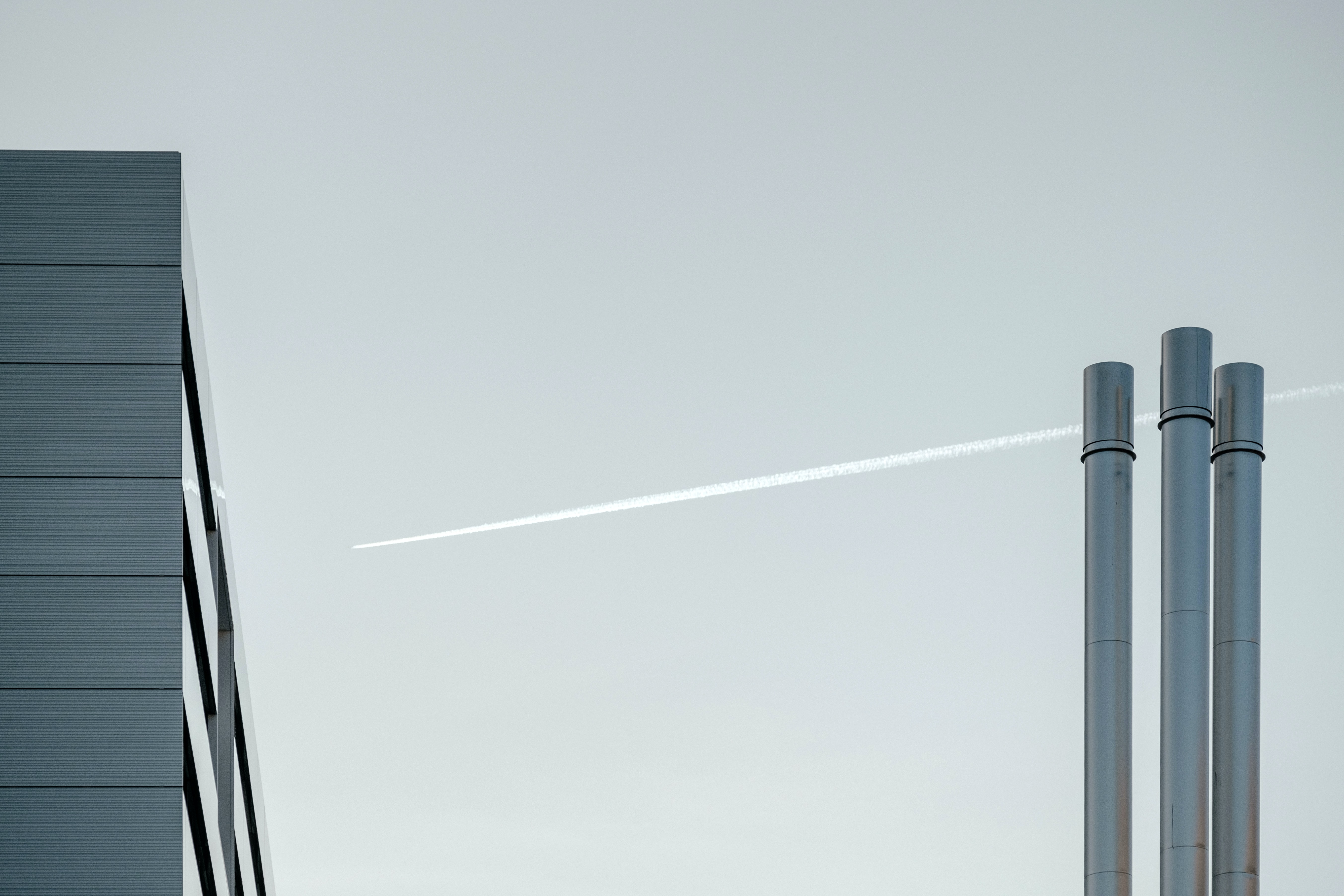 A plane with contrail is flying over an industrial building with chimneys in Geneva.