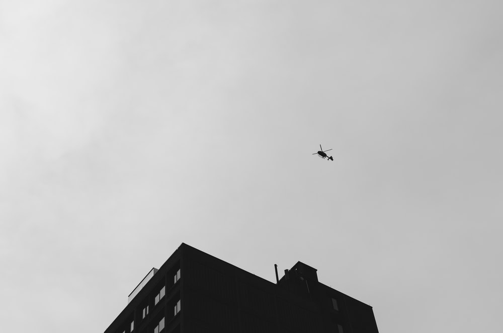 black helicopter flying under cloudy sky during daytime
