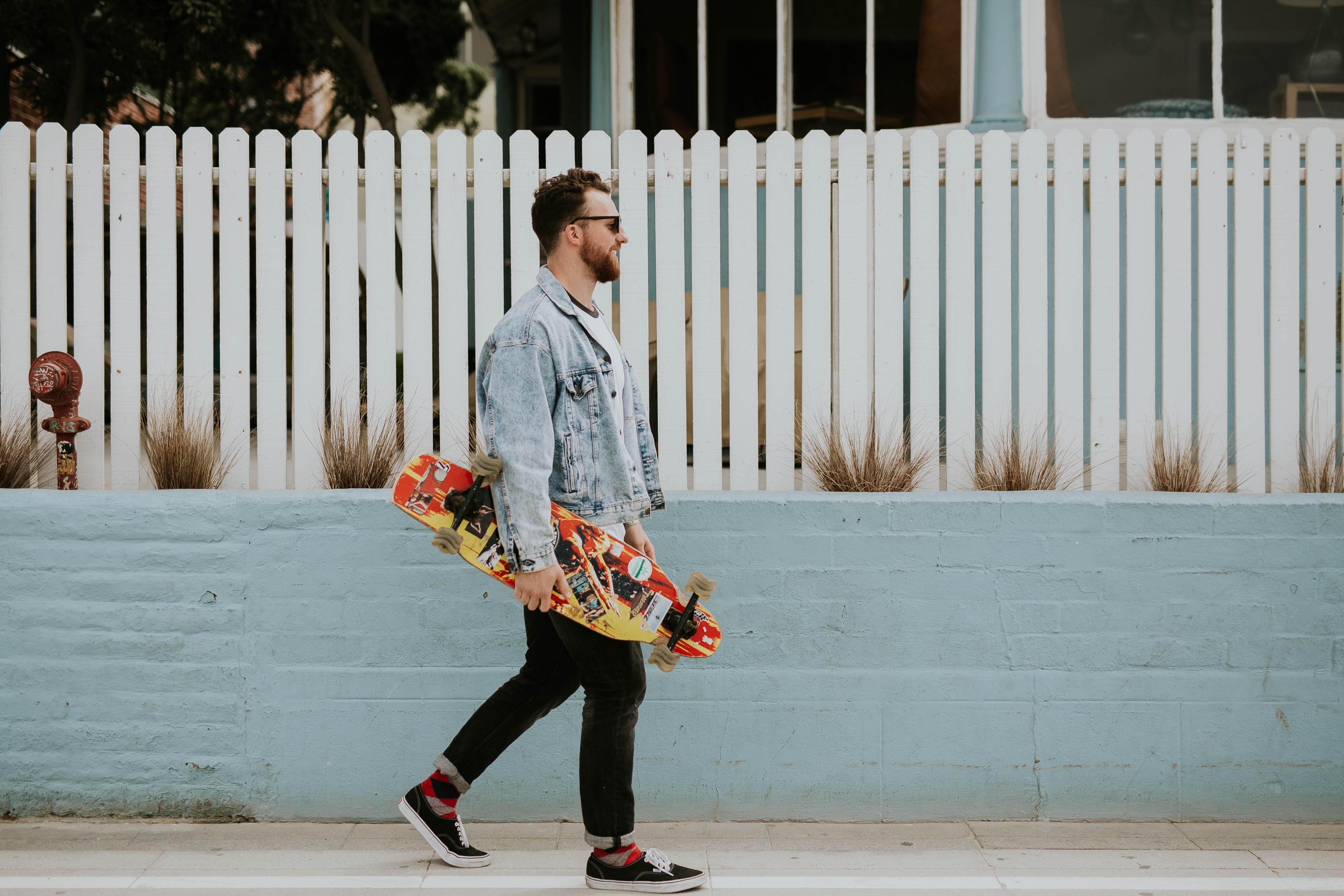 man carrying long board walking beside white fence