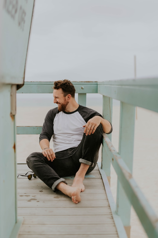 man smiling while sitting on floor during daytime