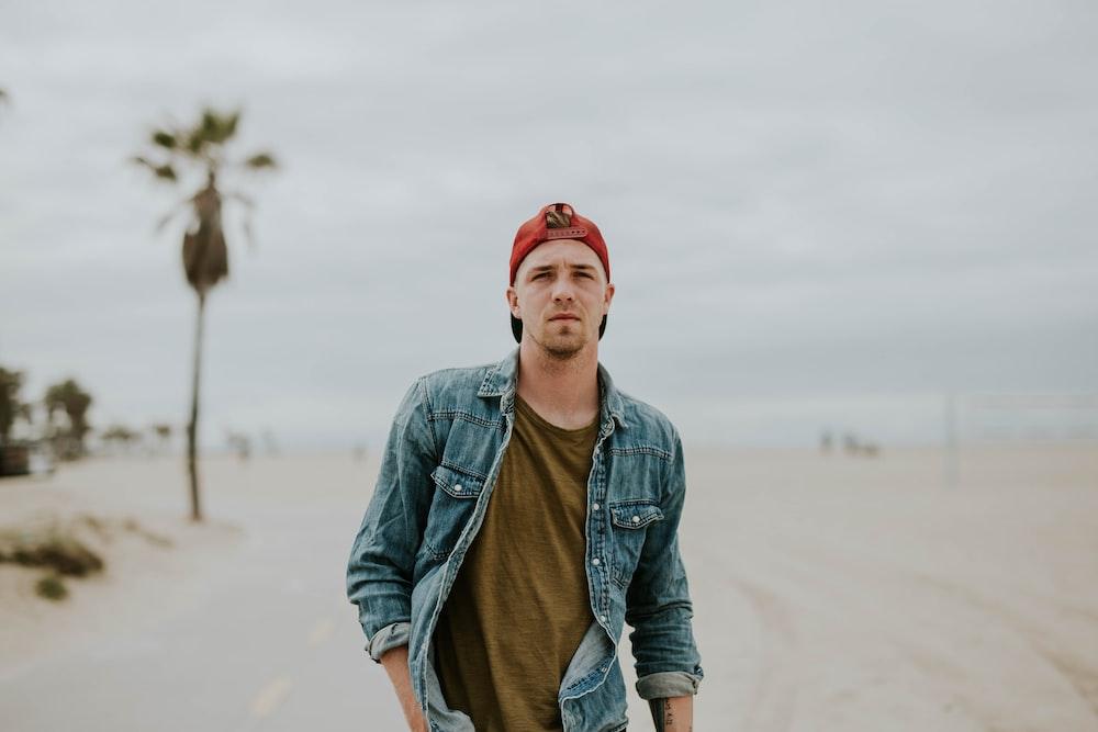man standing on road between sand