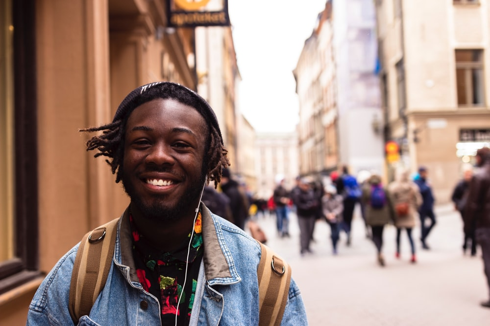 A young man in a jean jacket with a backpack and headphones smiles outdoors in Stockholm