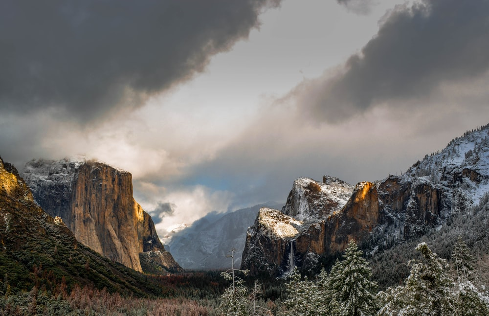 mountain covered with snow under black clouds during daytime