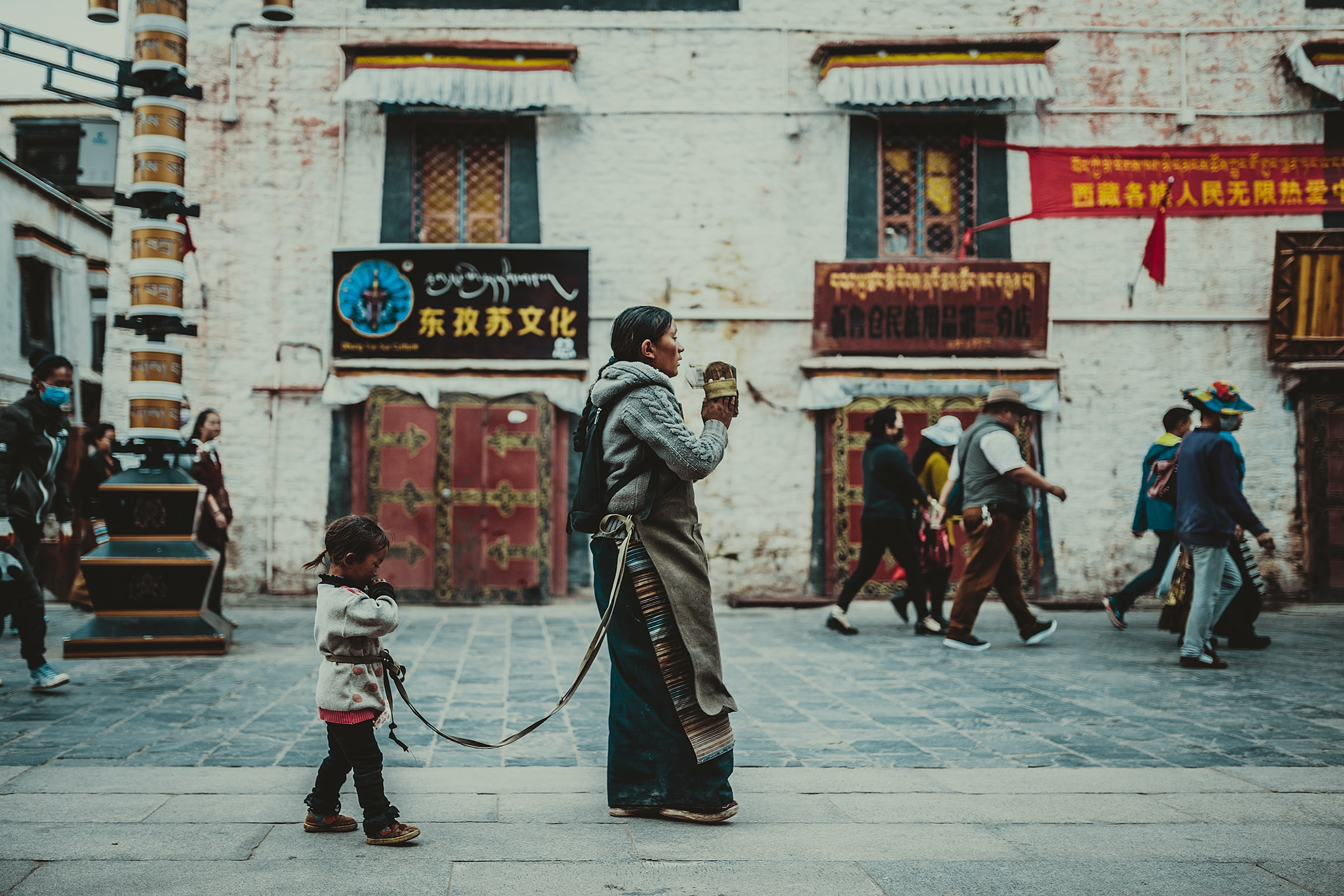 A woman with a child strapped to her walks down a crowded city street