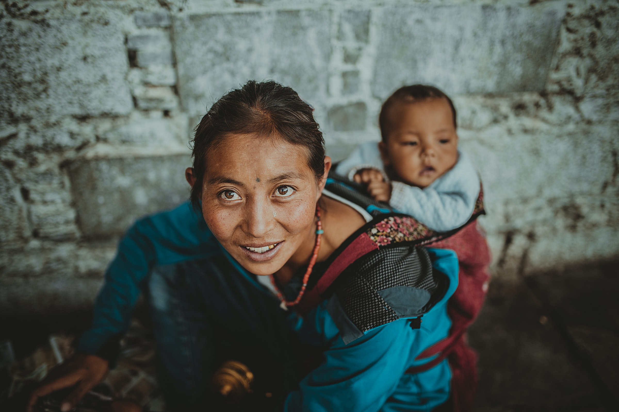 Himalayan woman on a stone staircase with her baby strapped to her back