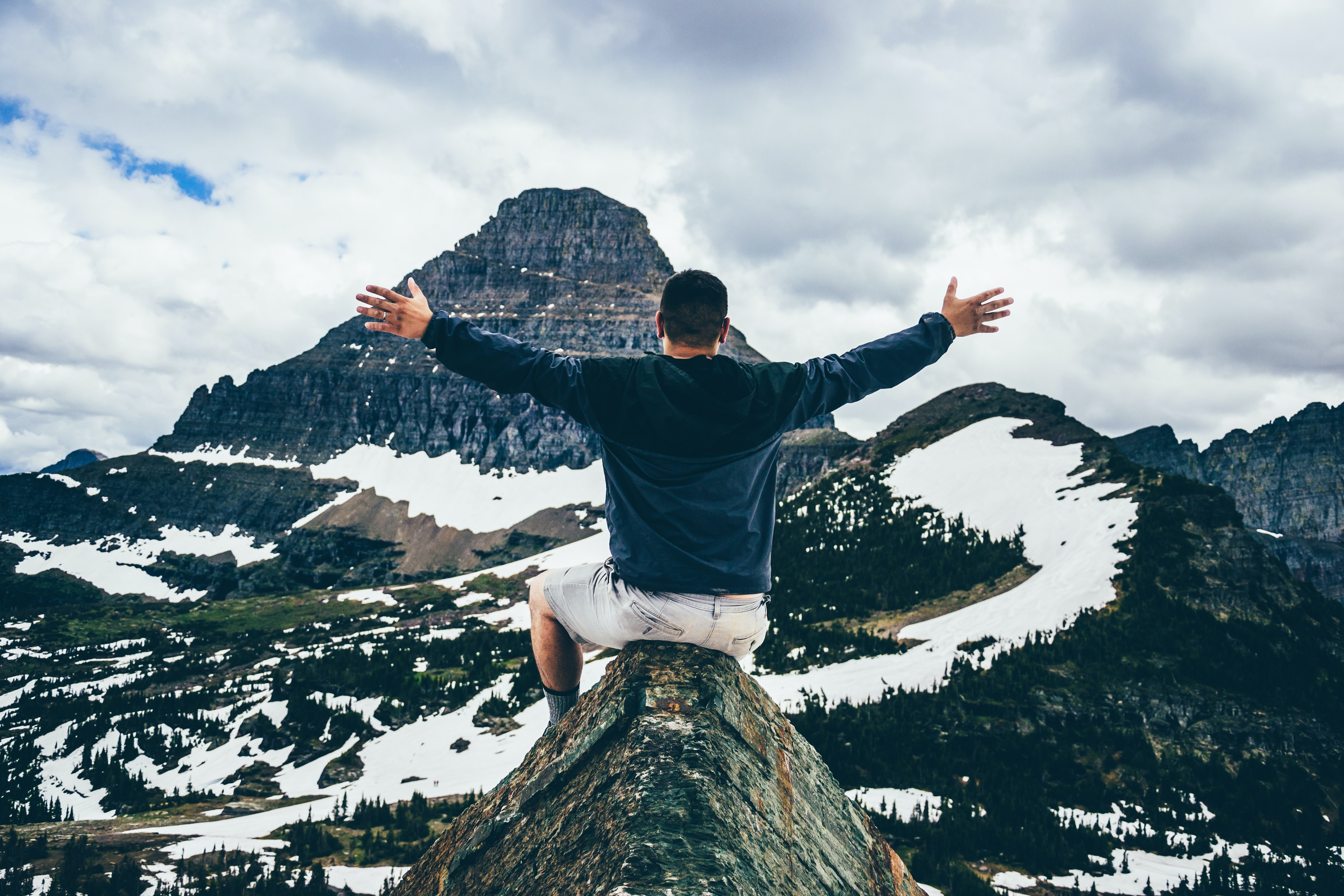man sitting on cone rock spreading hands