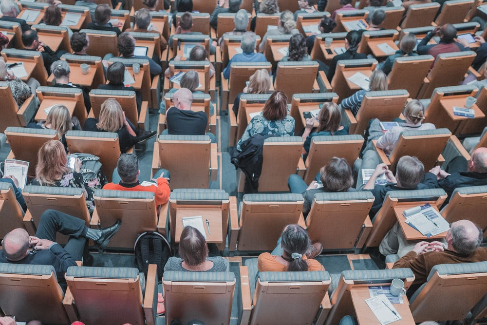 high-angle photography of group of people sitting at chairs
