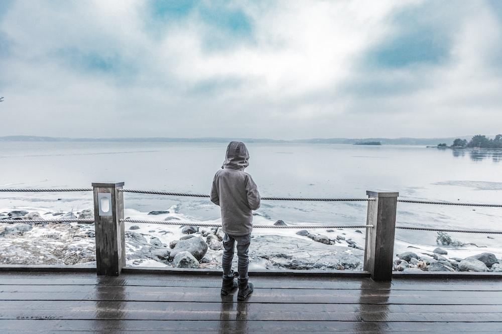 child standing infront of seashore on brown platform