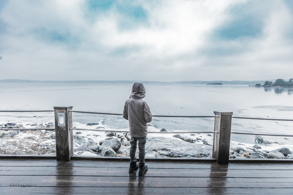 child standing infront of seashore on brown platform