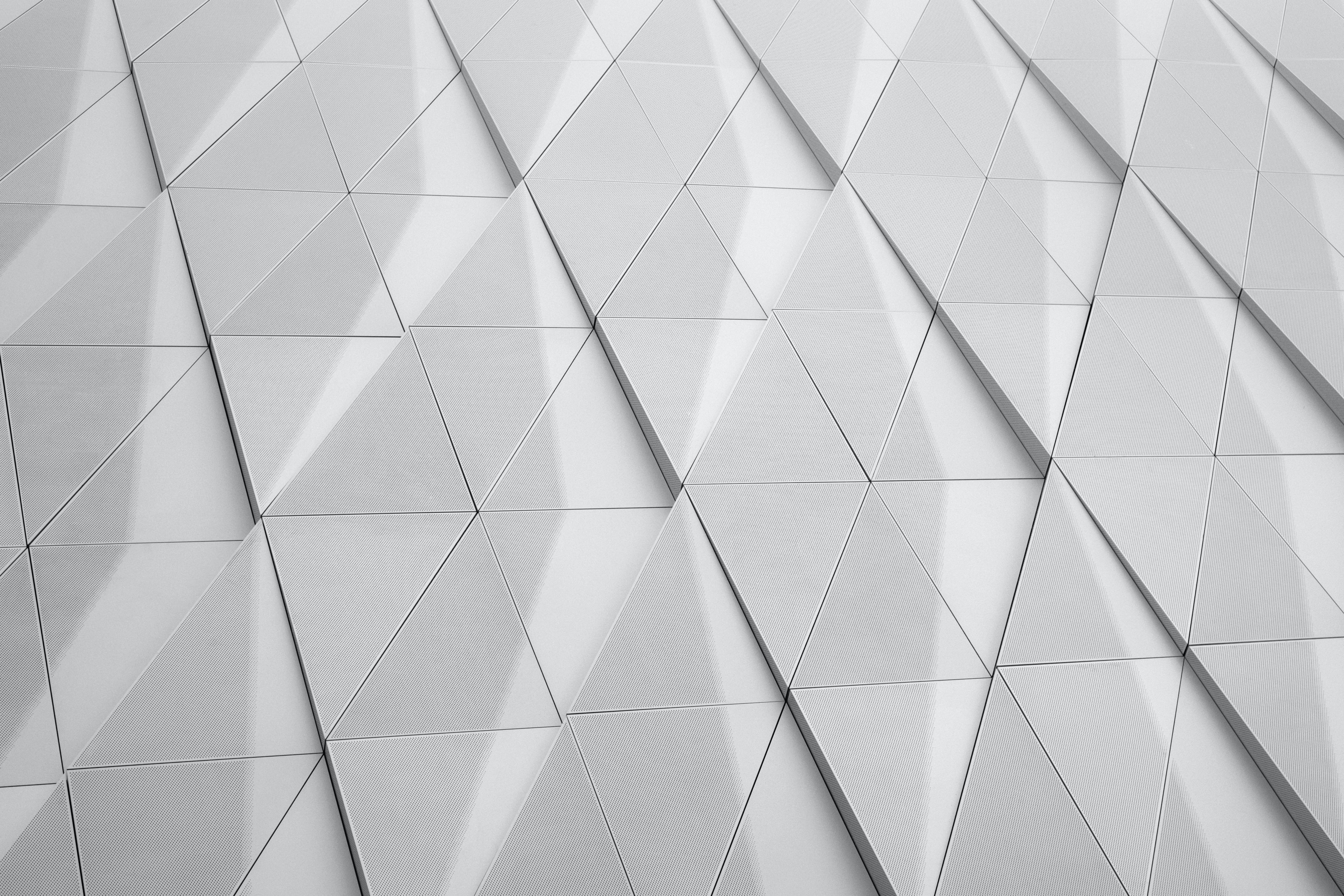A white facade with a geometric pattern made up of triangles