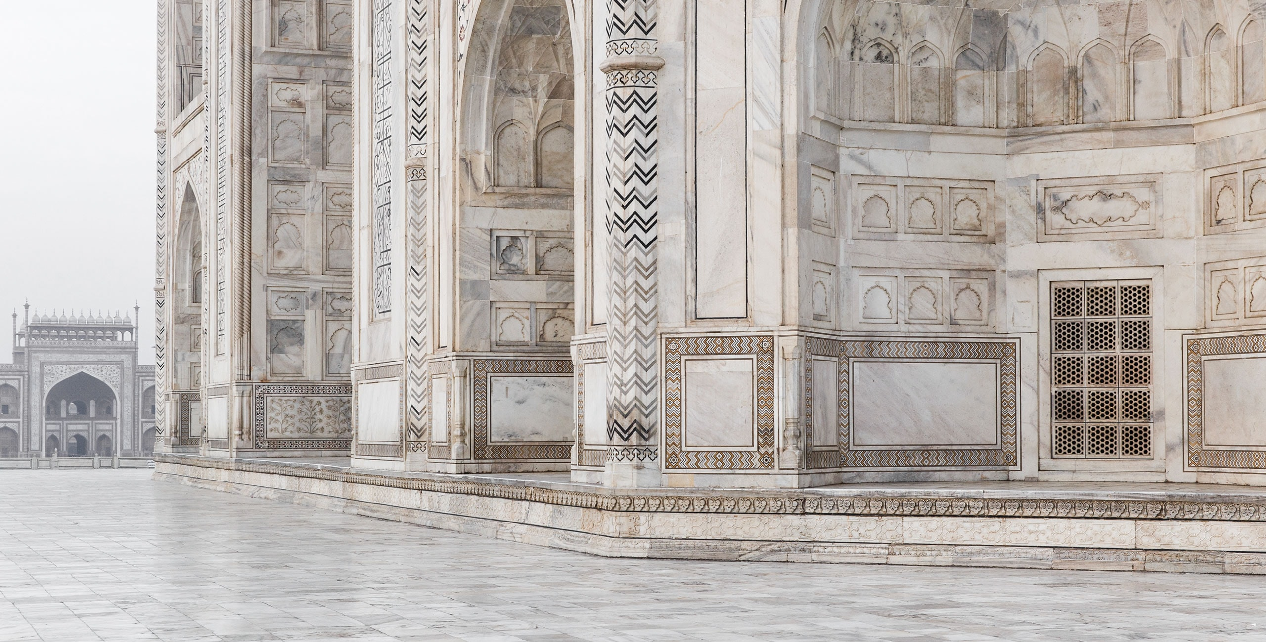 A historical, white structure that has a lot of unique details carved into the marble