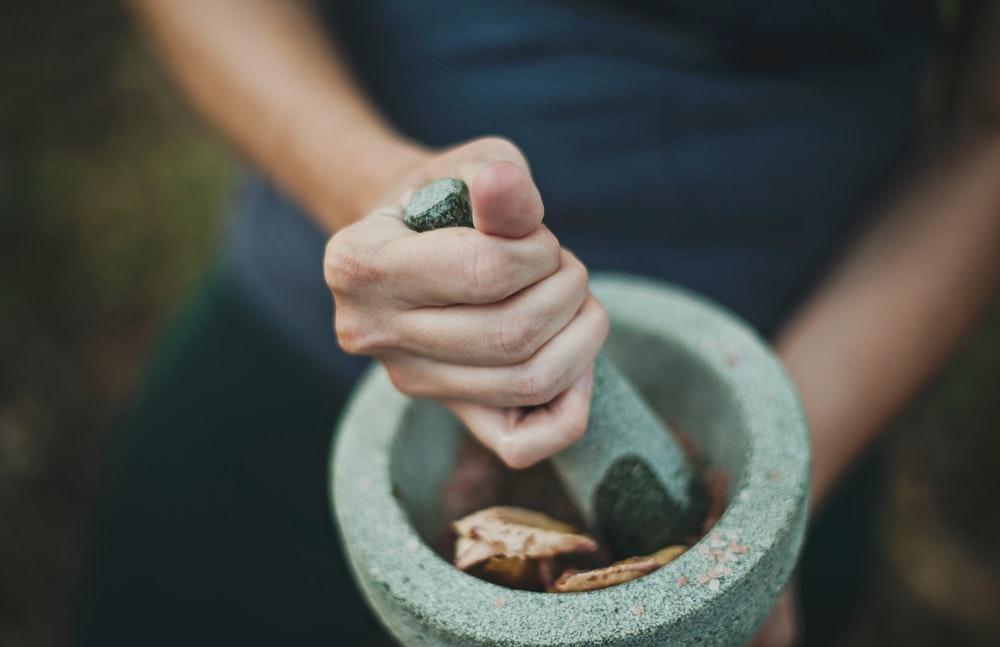 A person stirring mortar with a pestle in Bridgeport