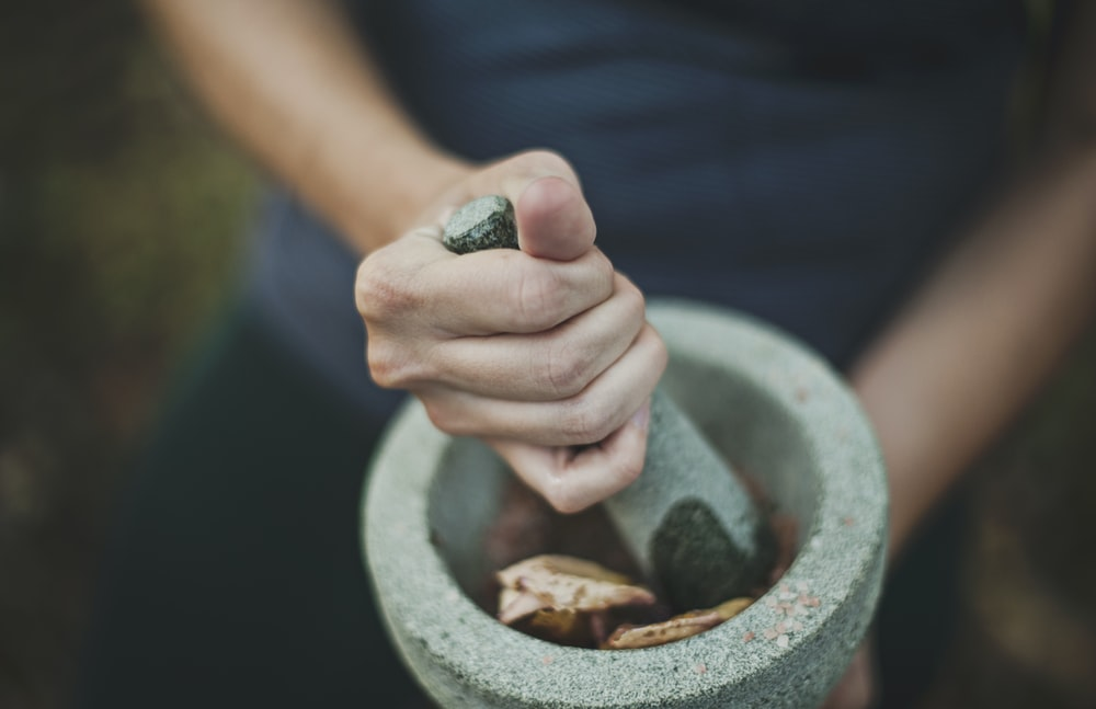 person grinding on mortar and pestle