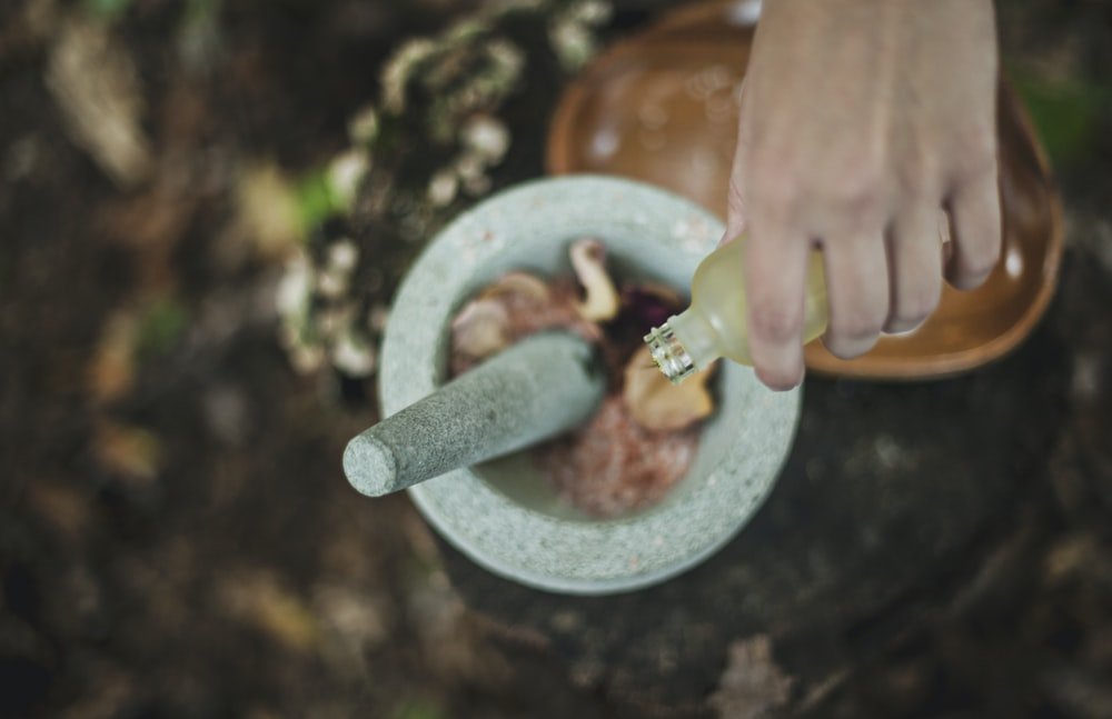 high angle photo of person pouring liquid from bottle inside mortar and pestle