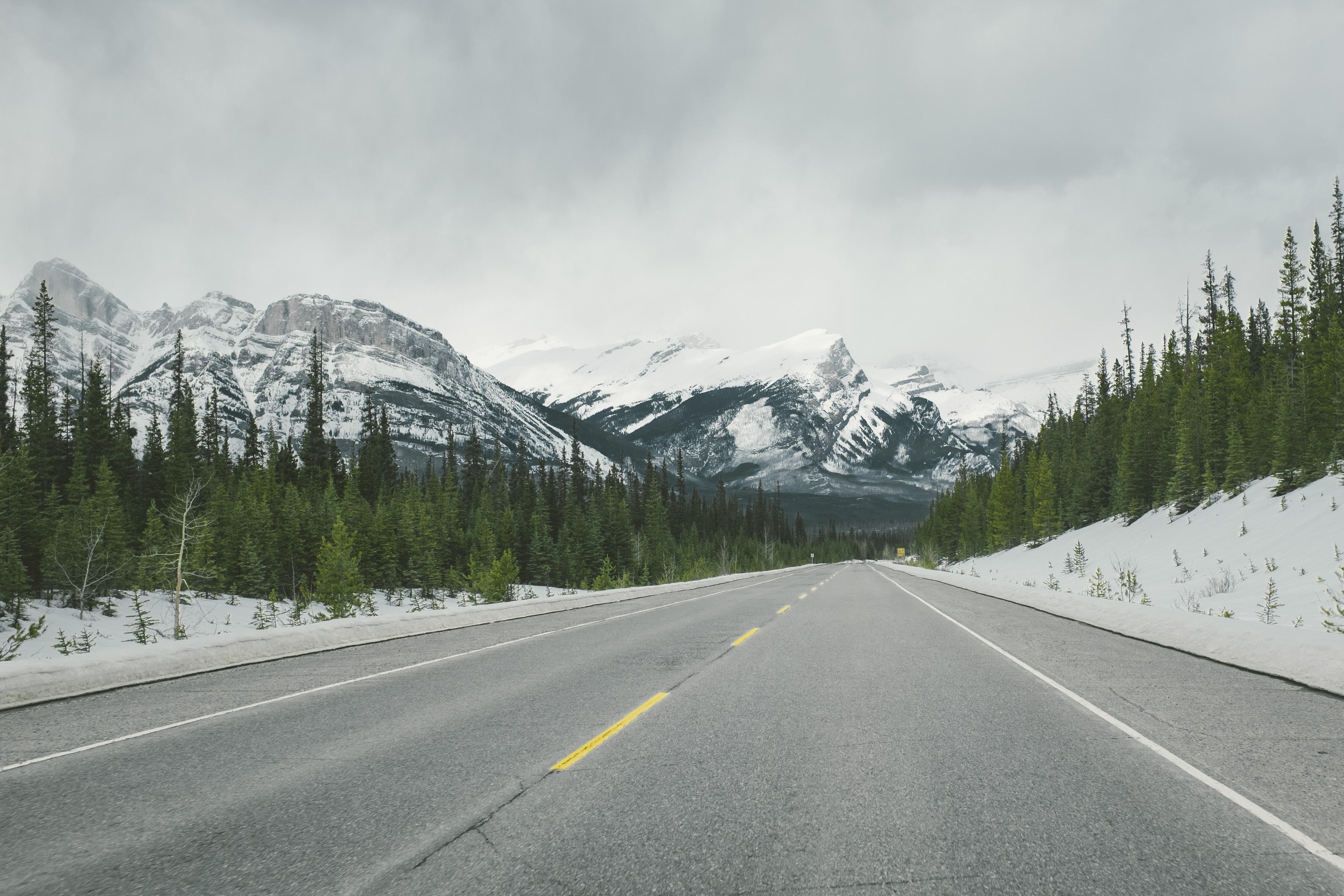 snowy mountains across asphalt road