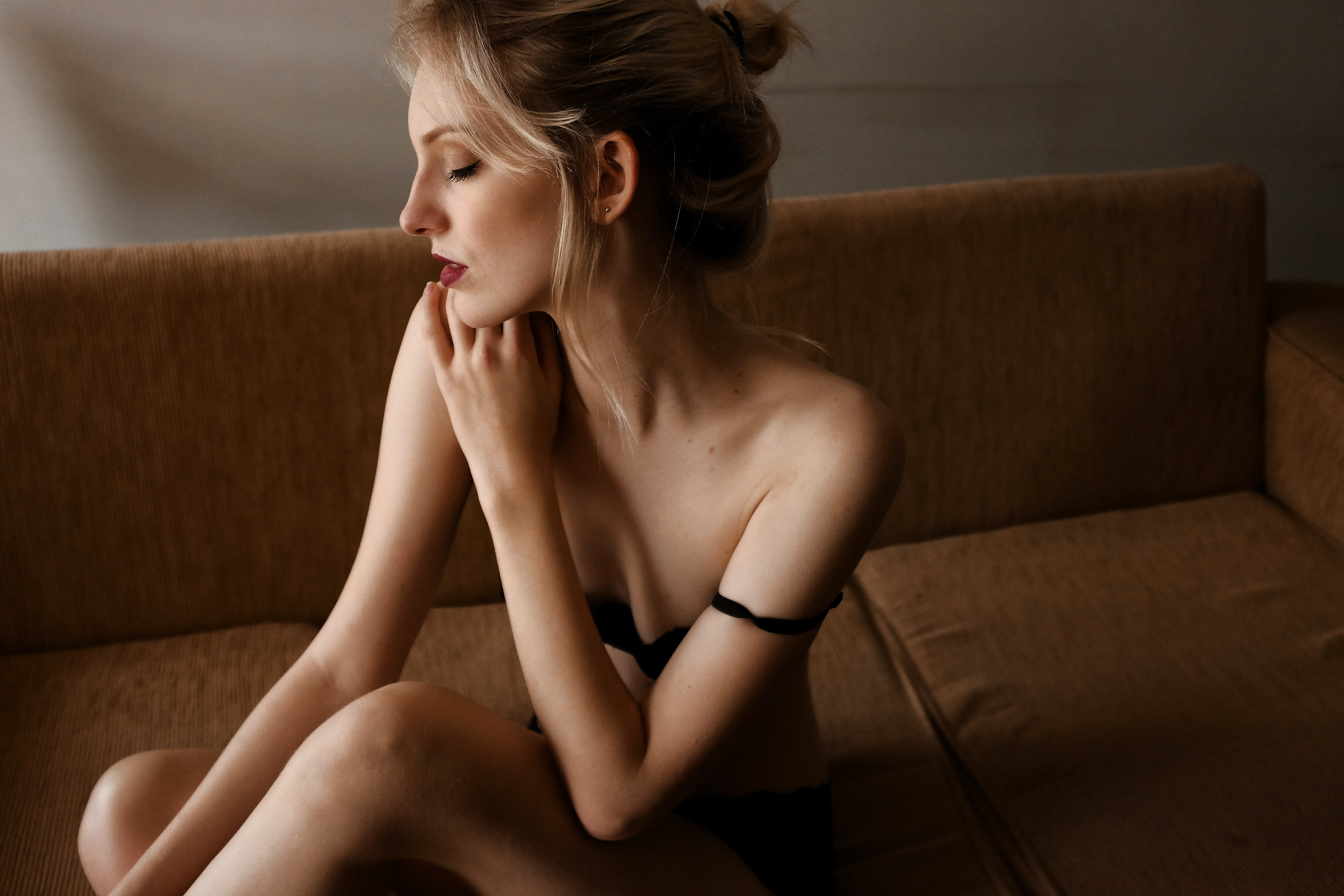 Woman poses seductively with eyes closed wearing in lingerie on her couch
