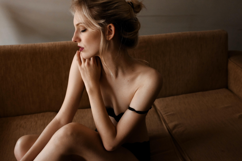 woman wearing black underwear sitting on brown couch