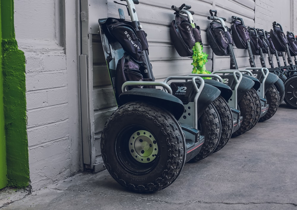 black segways parked beside gray wall