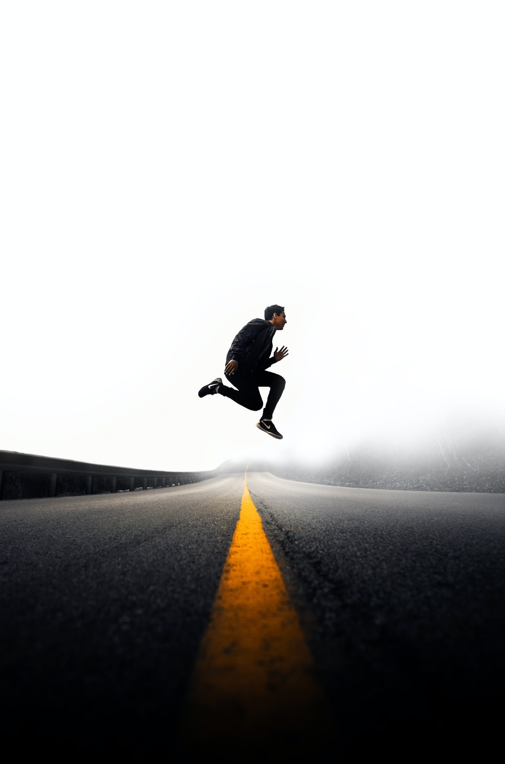 man jumping above gray and yellow concrete road at daytime