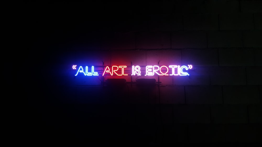 All Art is Erotic neon signage on brick wall