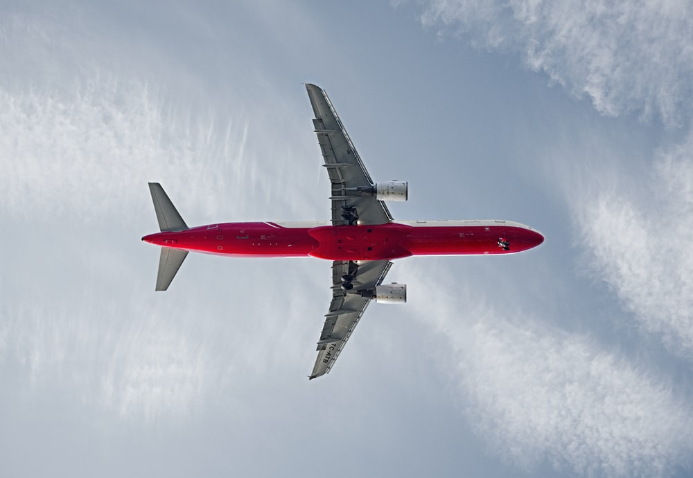red and white passenger airplane on the sky during daytime