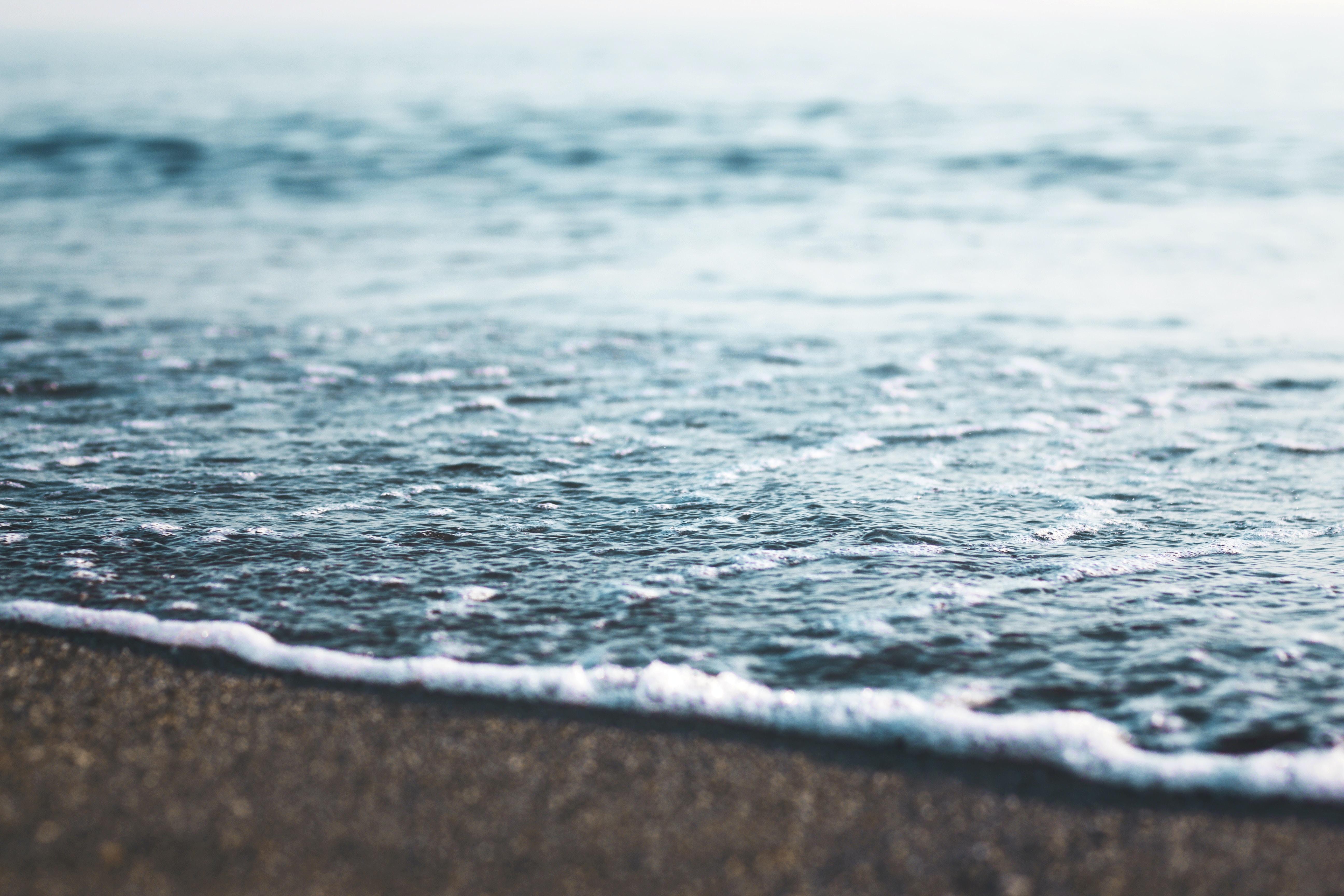 sea waves touches seashore at daytime