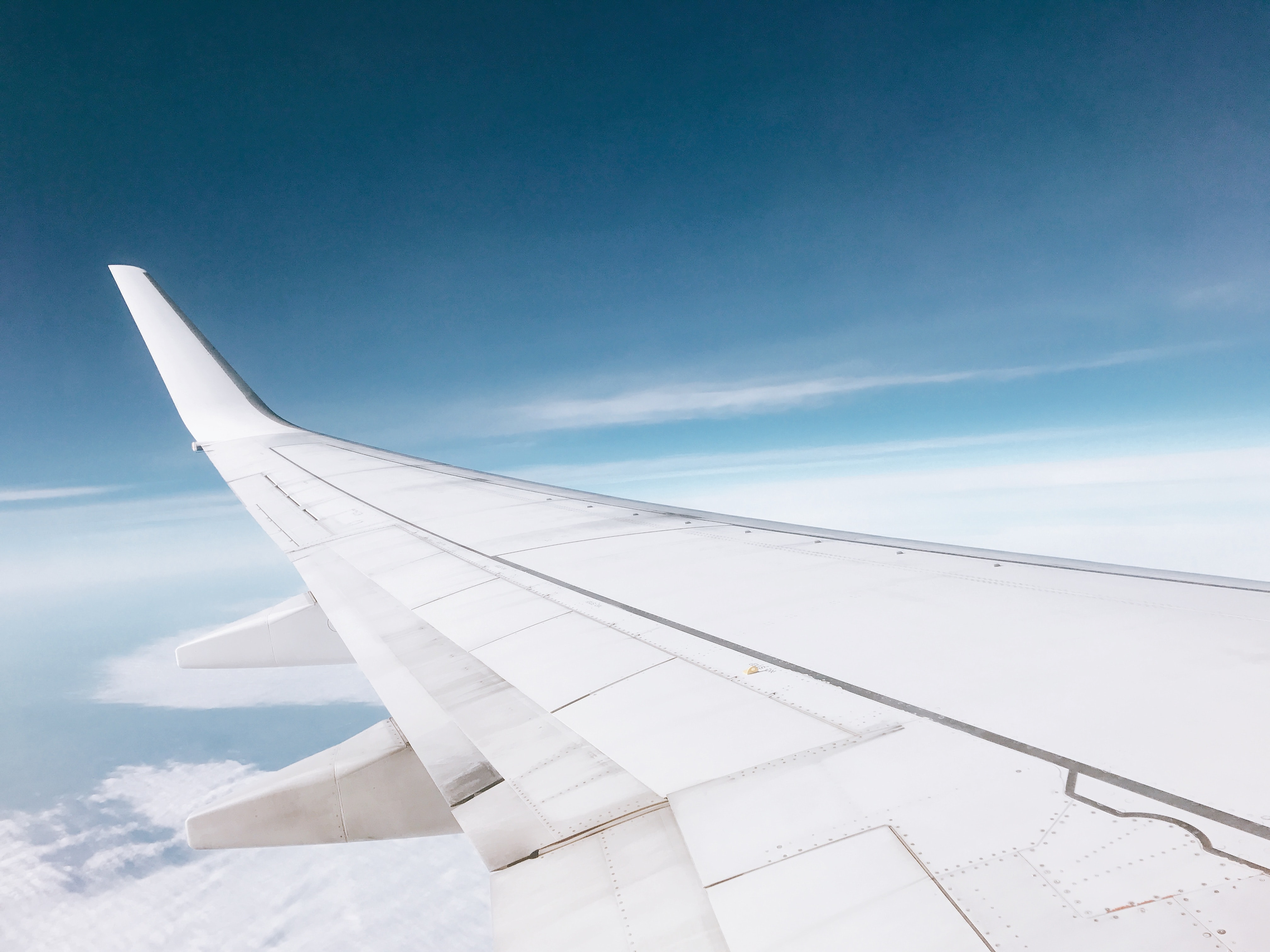 white airplane flying over white clouds