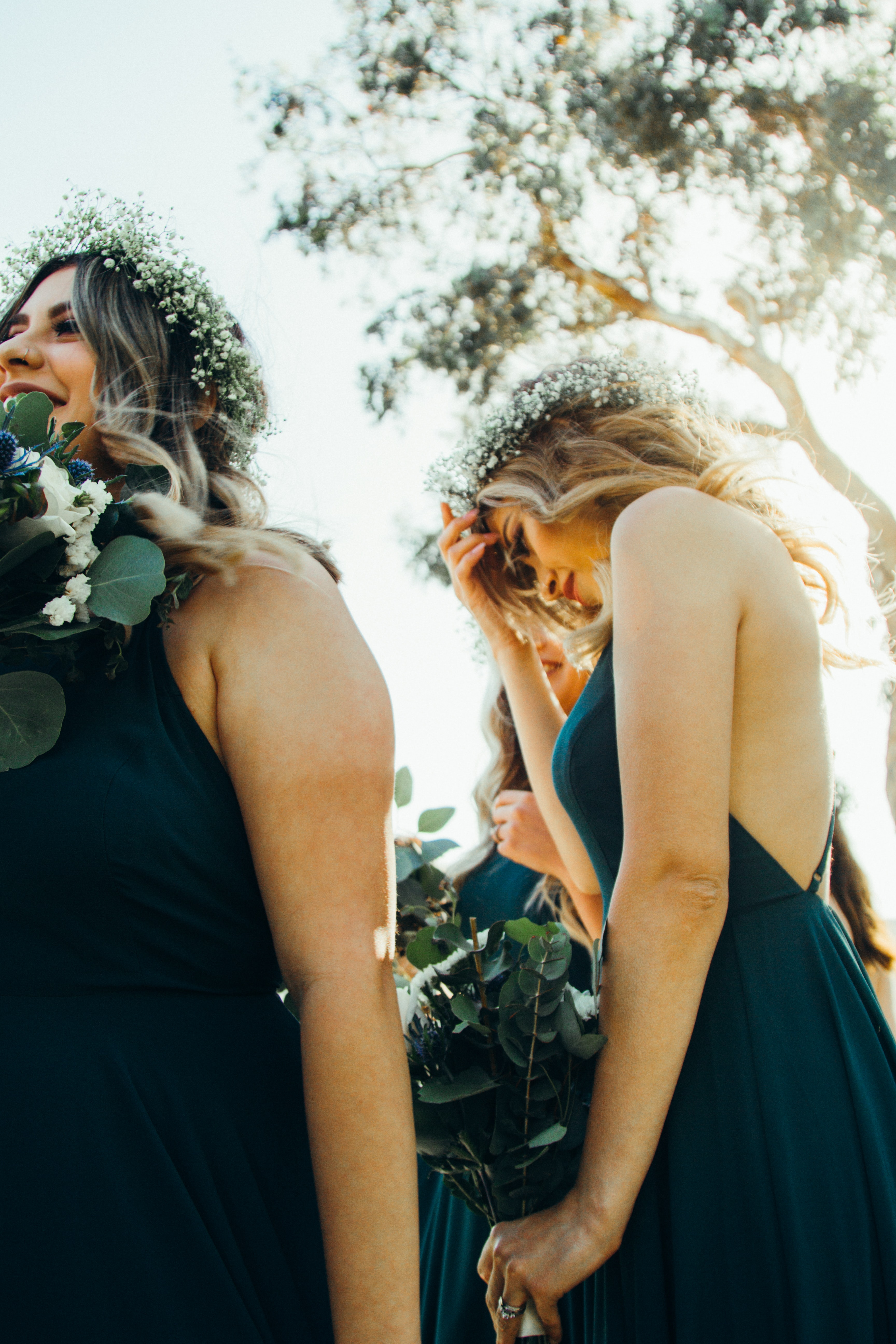 Bridesmaids wearing pretty dresses and flower crowns, enjoying themselves beneath a tree