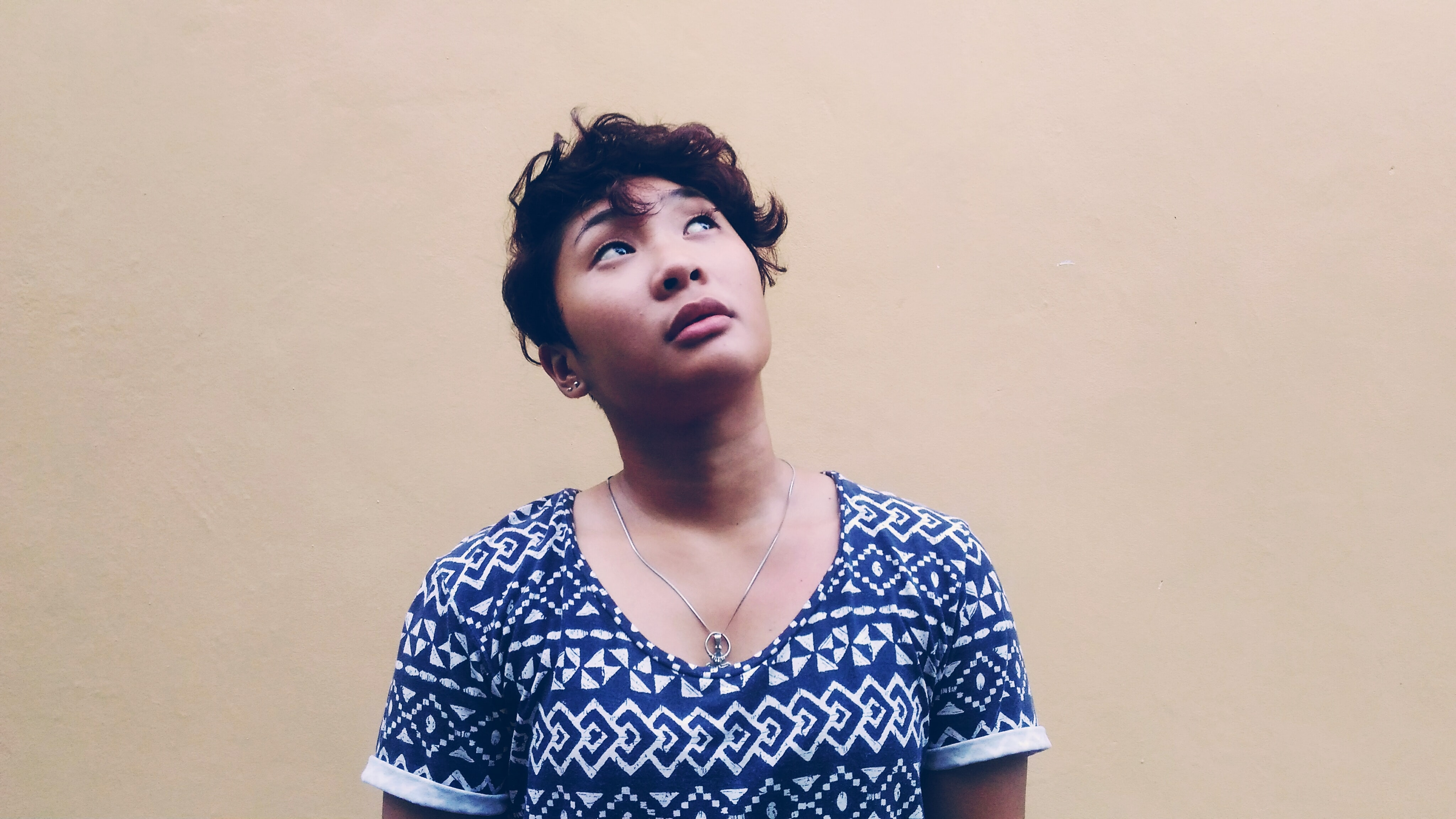 A woman with short hair looks upward in front of a light-colored wall in Bacong