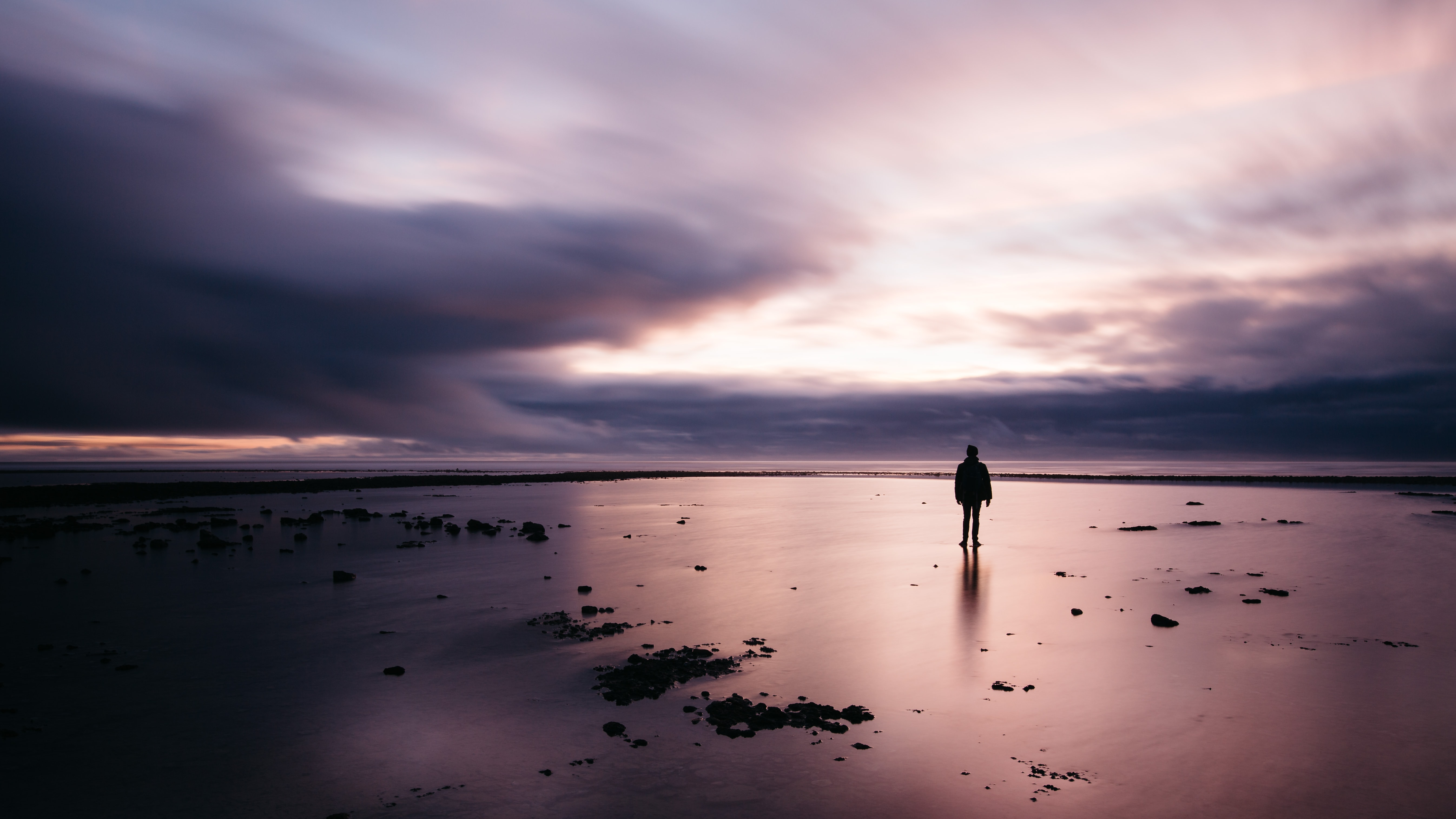 A lone man standing on a beach looking into a cloudy evening sky in Grignon