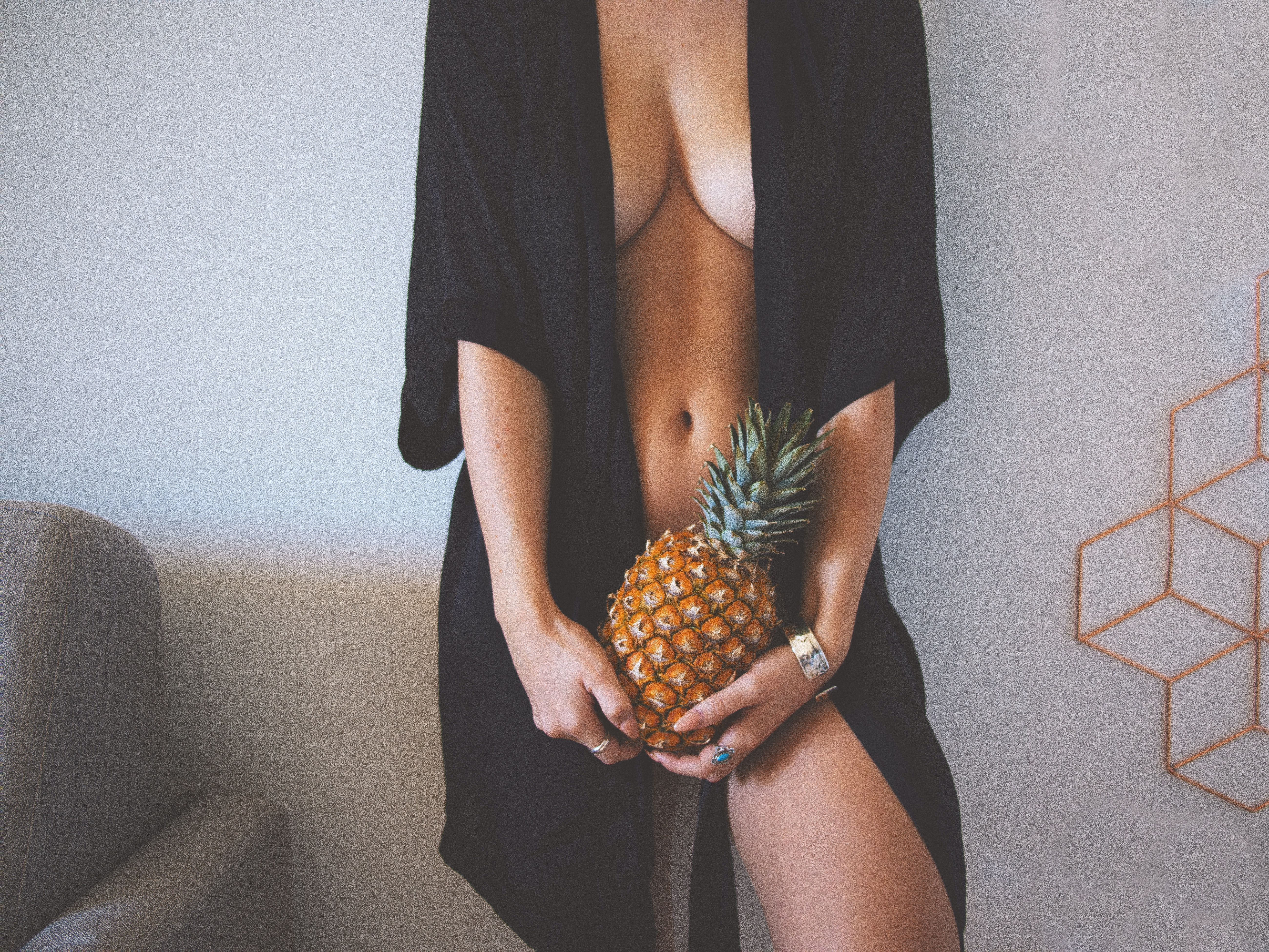 Naked woman in a robe holding a pineapple