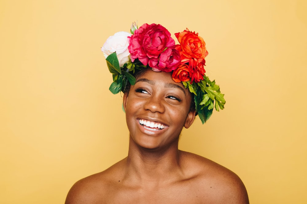 African-American woman smiling and laughing with flower crown on her head