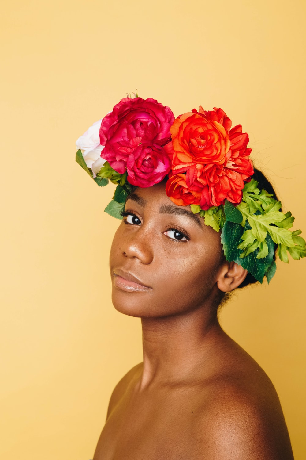 An African American woman with a flower covered headband.