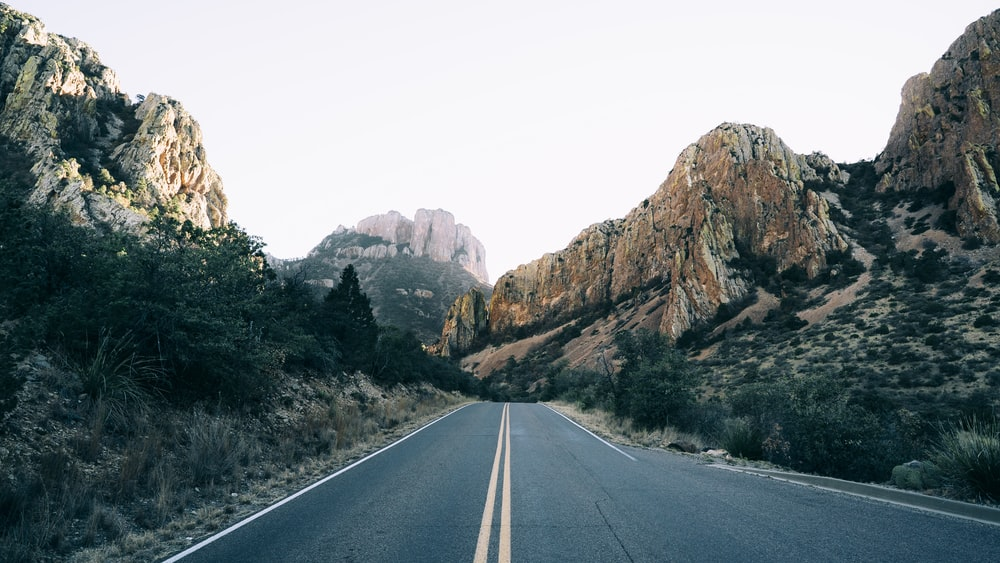 road lined with rocky mountain at daytime