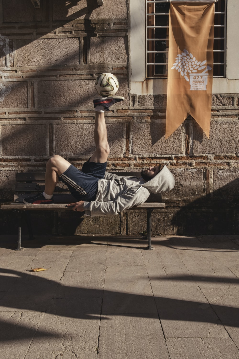 man in gray hooded jacket and black shorts playing ball while lying on bench