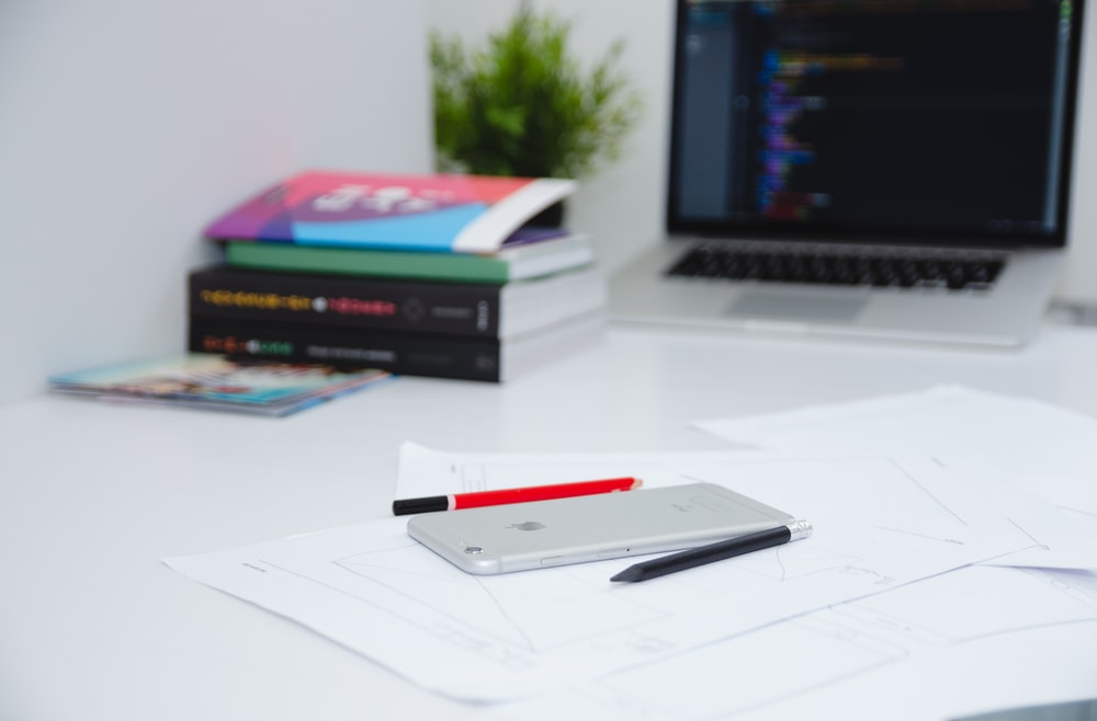 A smartphone on top of papers next to a laptop, books and pens.
