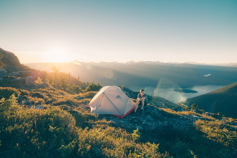 man sitting on stone beside white camping tent