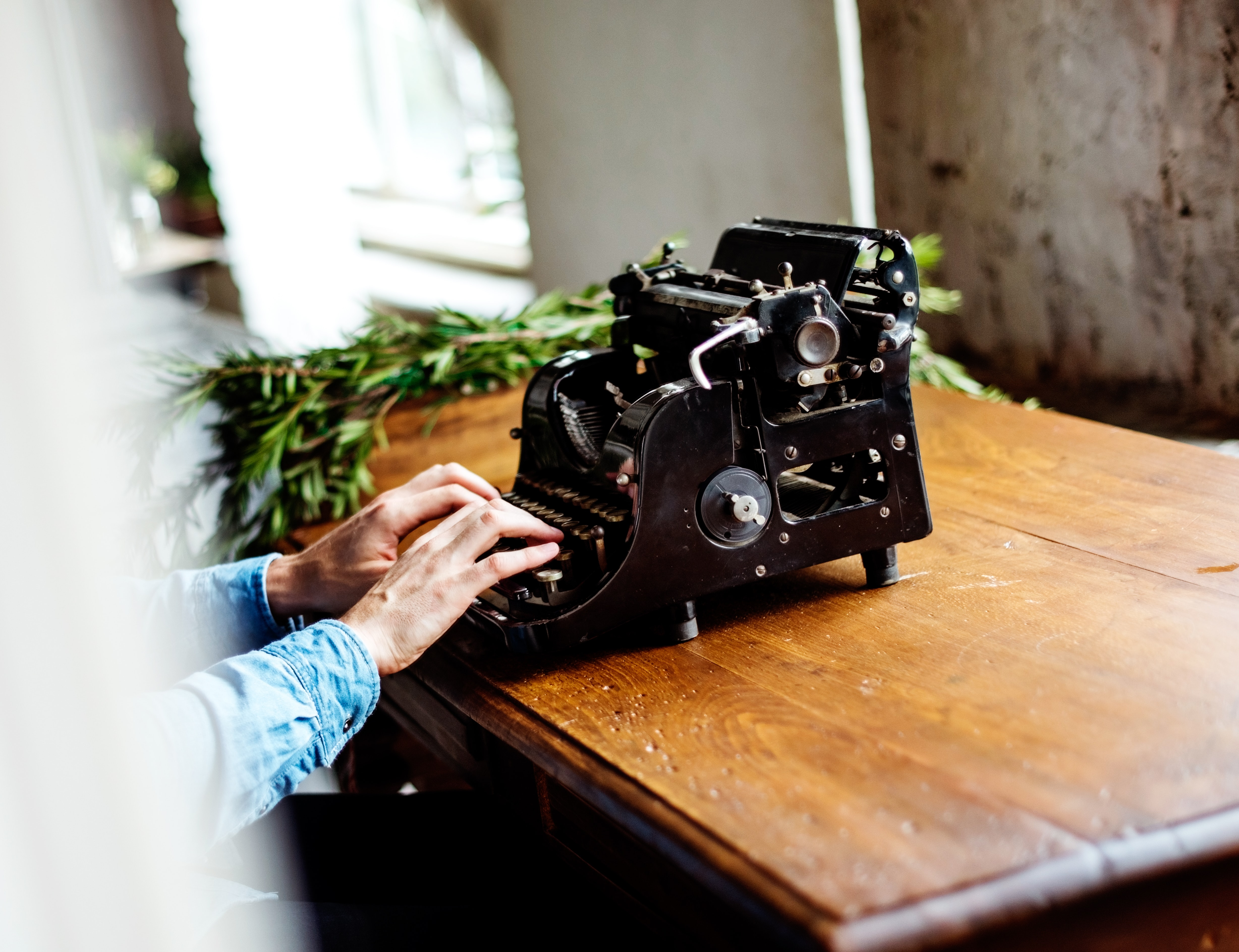 A person types on a vintage typewriter at a desk